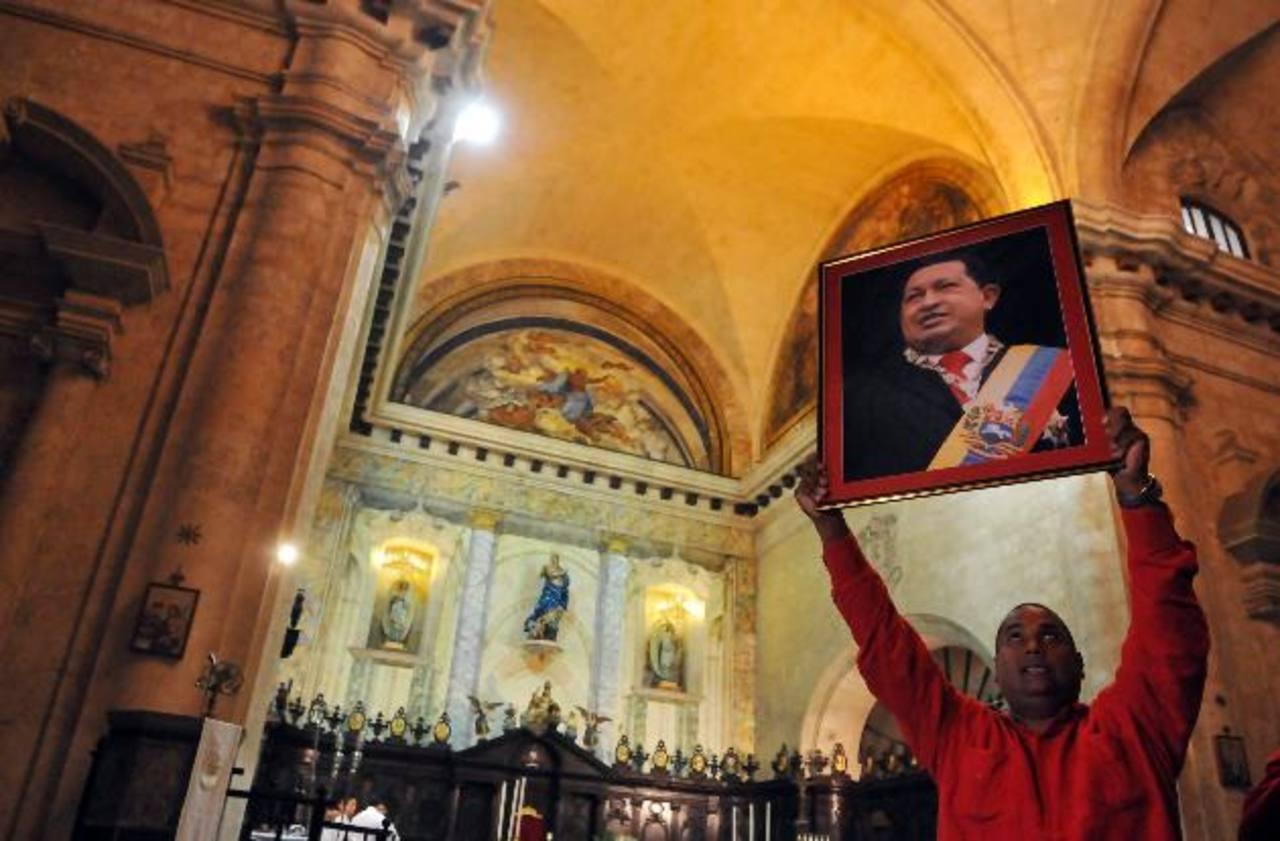 Hombre sostiene una fotografía del gobernante de Venezuela, Hugo Chávez, mientras asiste a una misa en la catedral de La Habana (Cuba). foto edh / efe