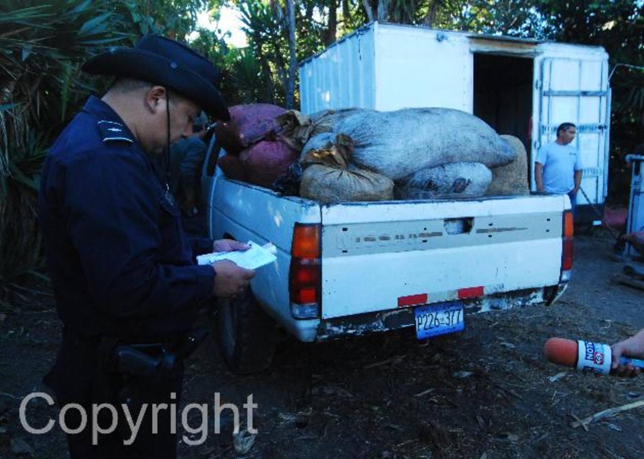 Un oficial de la Policía verifica que el cargamento de café que transporta este pick up no sea robado en la zona de El Boquerón, en el volcán de San Salvador. Fotos EDH / Marlon Hernández.