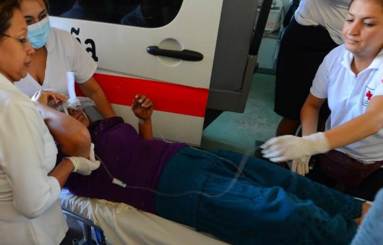 Una de las personas que resultó lesionada en el vuelco del autobús es auxiliada por personal médico. El percance provocó que 25 personas resultaran heridas, seis de ellas de gravedad. Foto EDH / Marvin Recinos
