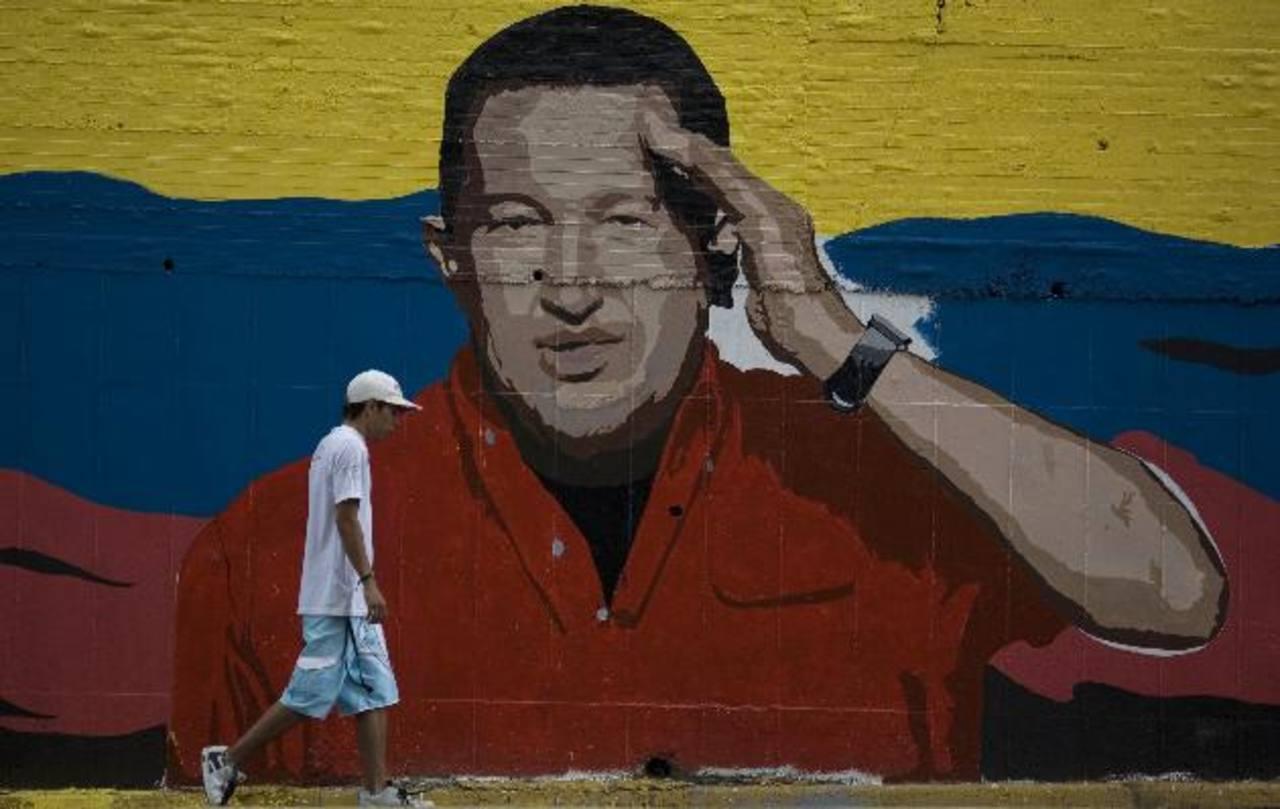 Un hombre camina frente a un mural con la imagen del mandatario venezolano. FOTO AP