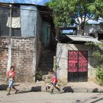 Dos niños caminan frente a la casa donde el martes fueron atacados un policía y su familia. Dos murieron. Foto EDH / Jorge Beltrán.