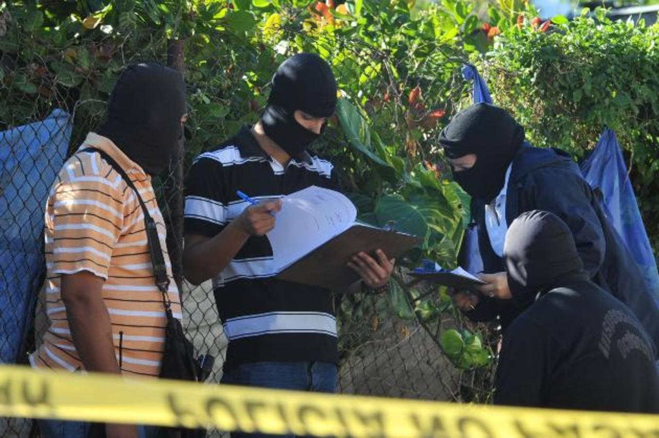 Investigadores de la Policía inspeccionan el lugar donde fue asesinado el profesor Adrián Aquino. foto edh / ericka chávez