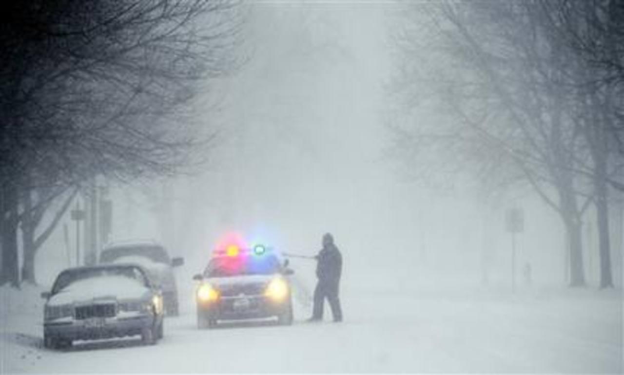 Un policía saca nieve de su patrulla al transitar en St. Joseph, Misurí, el jueves 21 de febrero del 2013.