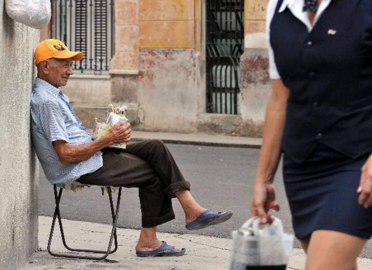 Este jubilado vende golosinas y cucuruchos de maní en una esquina en La Habana. foto edh / efe