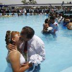 Parejas de recién casados se besan en el interior de una piscina pública durante una boda masiva en el Día de San Valentín en Lima, Perú. Foto/ Reuters