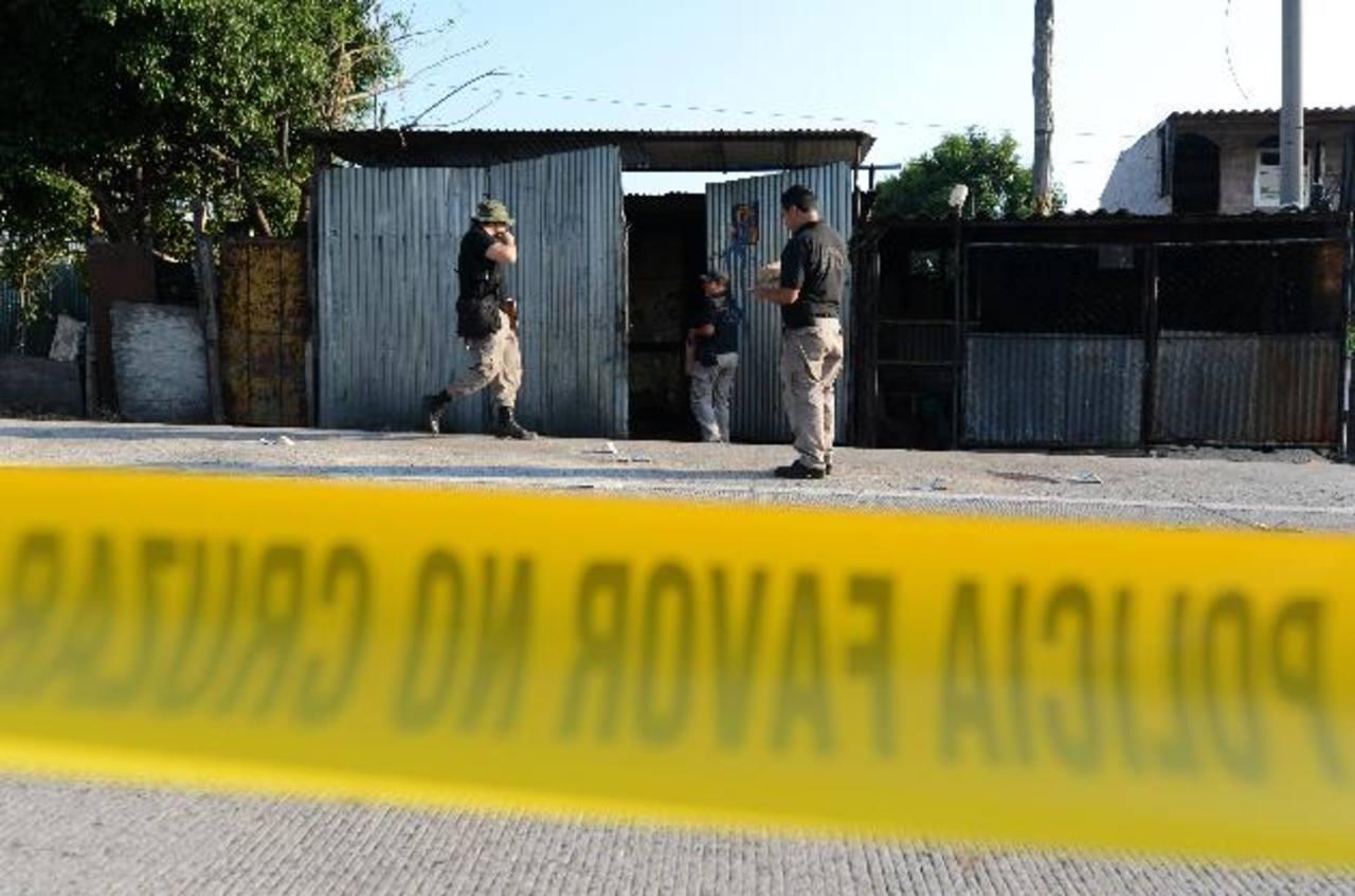 Policías recogen evidencias en el lugar donde ayer en la tarde fueron atacadas dos personas, dueñas de un taller en Ilopango por negarse a pagar la extorsión. Foto EDH / Jaime Anaya.