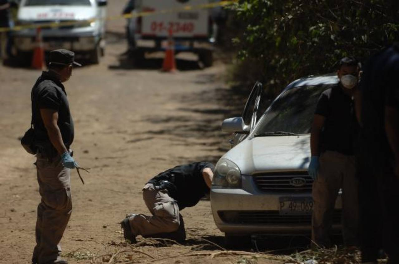 Policías inspeccionan el auto que manejaba un exmilitar estadounidense, asesinado en Izalco, Sonsonate. El homicidio ha alertado a las autoridades. Foto EDH / Archivo