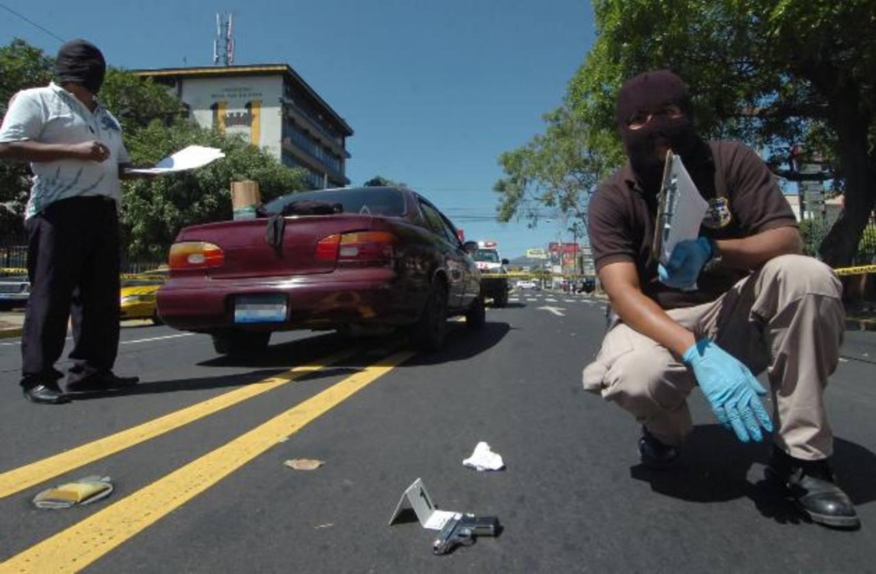 Investigadores observan la pistola que le decomisaron a los tres detenidos en la alameda Roosevelt. La PNC sospecha que son parte de una banda de asaltantes. Foto EDH / Éricka Chávez