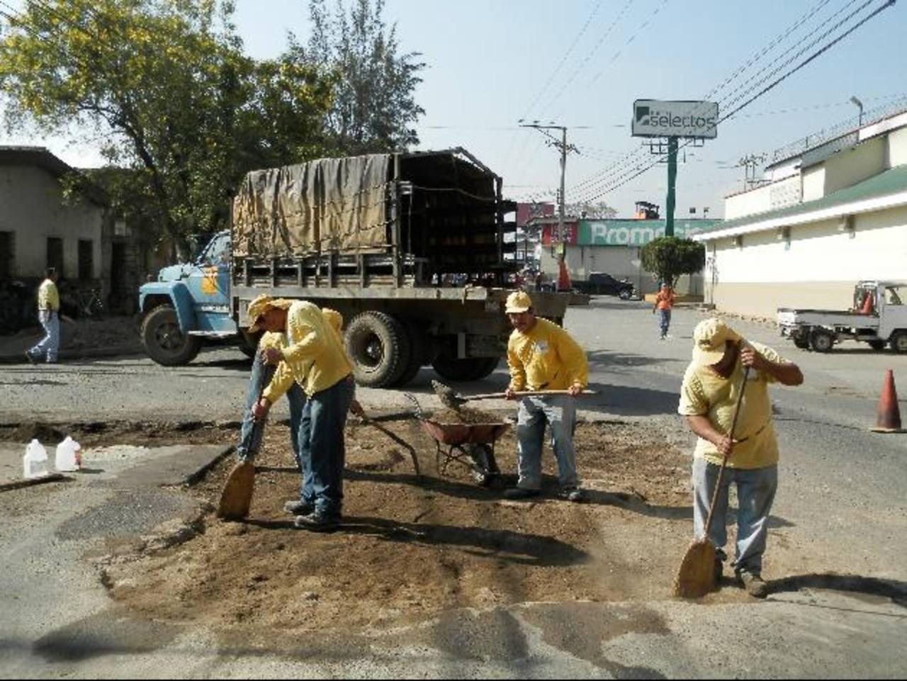 Trabajadores del MOP reparan uno de los agujeros dejados por Anda en la 11a Calle Poniente. Foto EDH / milton jaco