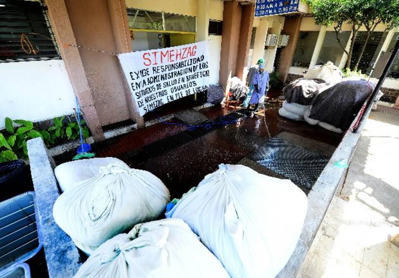 Un empleado de lavandería limpia el piso donde permanecen promontorios de ropa sucia. Foto EDH / Mario Amaya