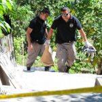 Agentes policiales cargan con algunas evidencias que hallaron cerca del cadáver de un desconocido, encontrado ayer en una zona rural del municipio de Ilopango. Foto EDH / Mauricio Cáceres