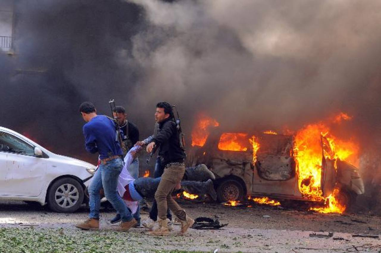 Tres rebeldes sirios llevan a un hombre que resultó herido tras la explosión del coche bomba. foto edh / AP