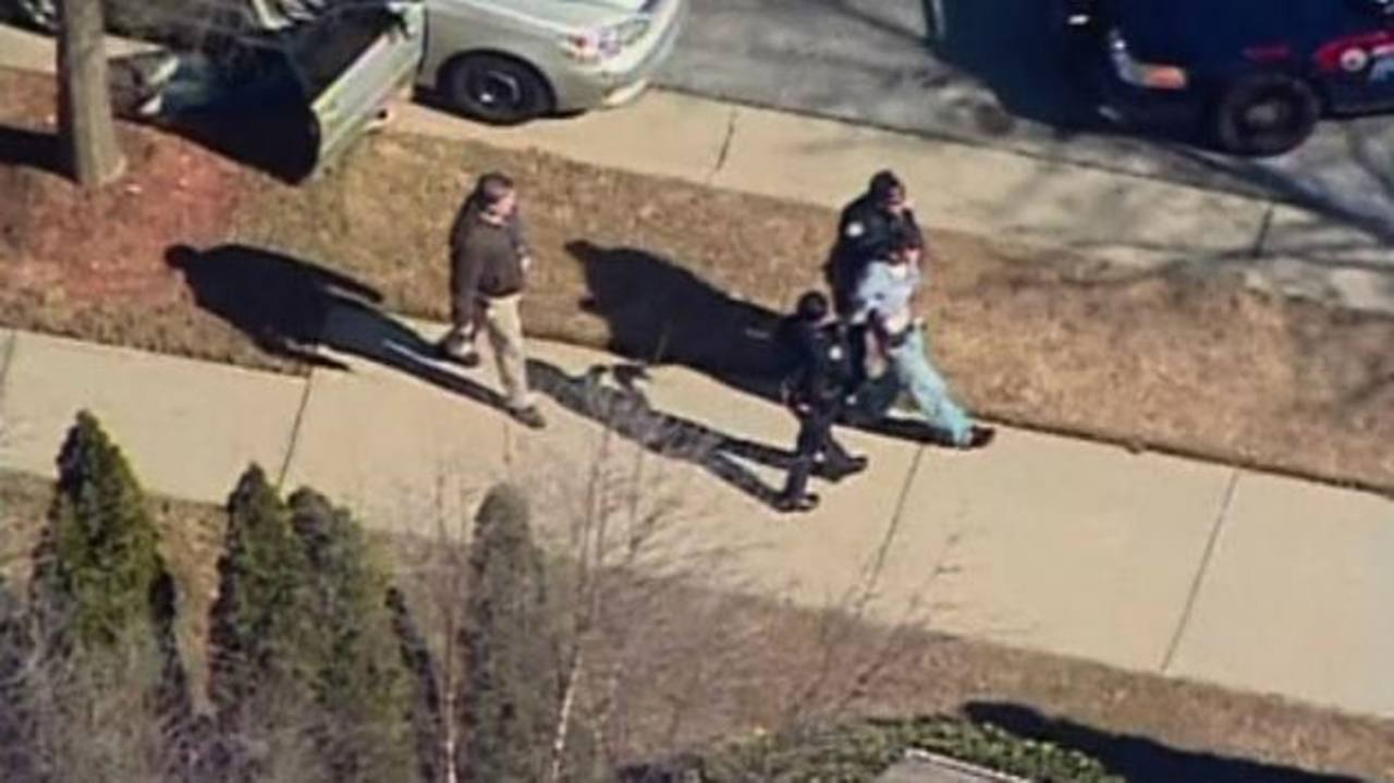 Socorristas trasladan al joven de 14 años herido. Agentes custodian a un sospechoso del tiroteo en la escuela de Atlanta. Fotos EDH / REUTERS