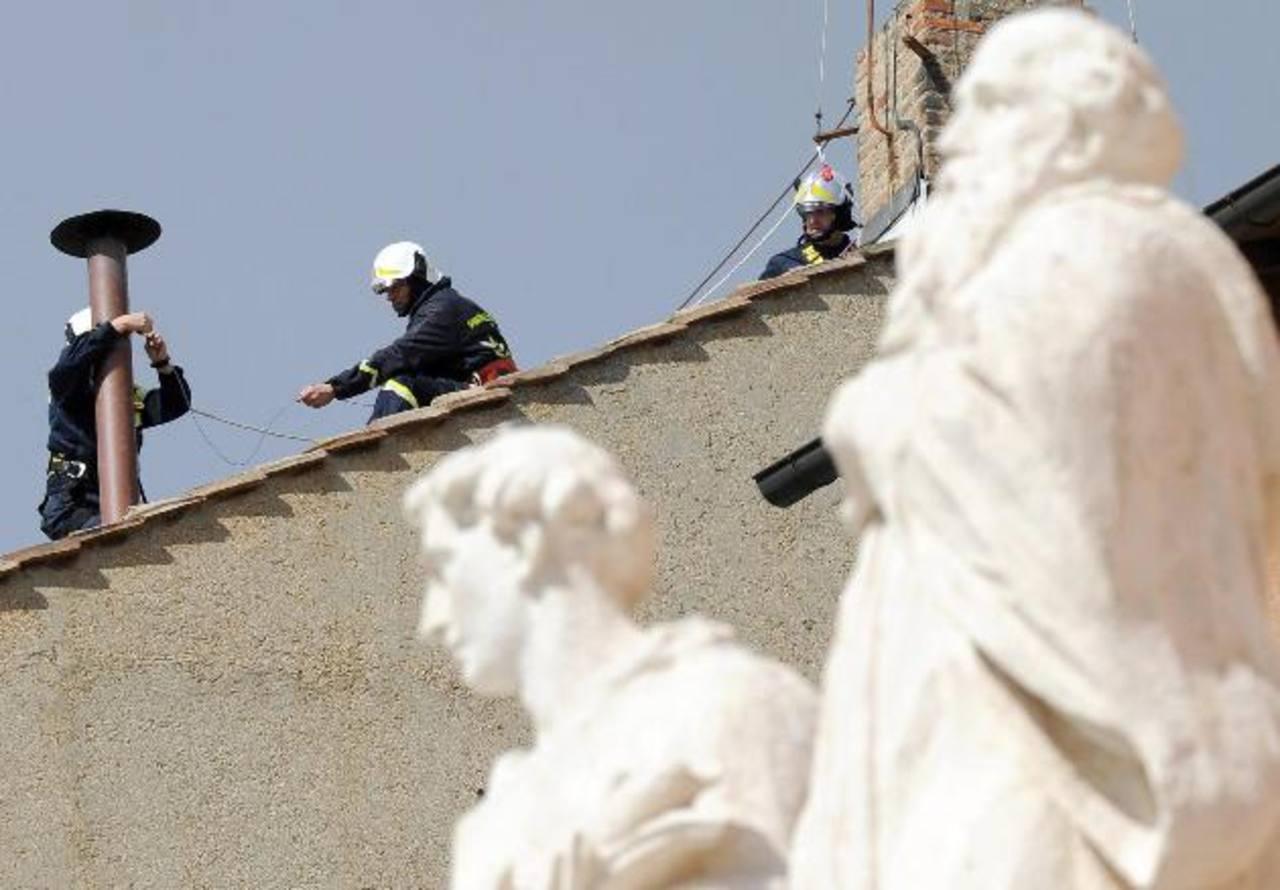 Bomberos colocan las chimeneas en el tejado de la capilla Sixtina por donde se verá el humo que indica si hay Papa. foto edh/efe