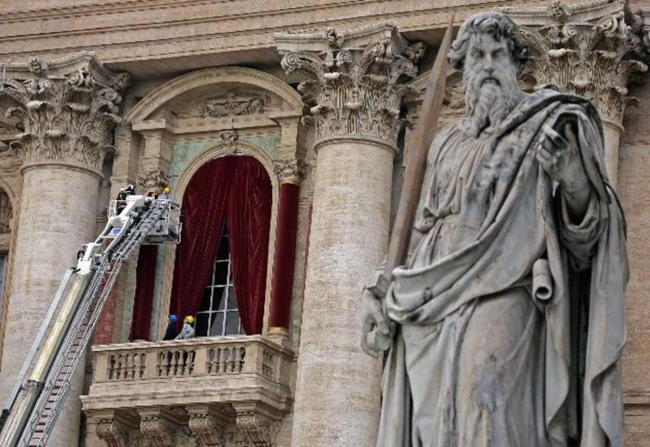 Bomberos decoran con terciopelo rojo el balcón central de la Basílica de San Pedro, en la Ciudad del Vaticano. foto edh / reuters