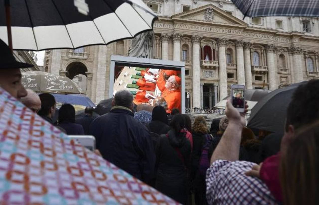 Varias personas observan una pantalla gigante instalada en la plaza de San Pedro, en Ciudad del Vaticano. Foto edh efe