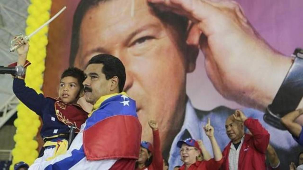 Nicolás Maduro carga a un niño vestido como Simón Bolívar durante un mitin proselitista. FOTO EDH