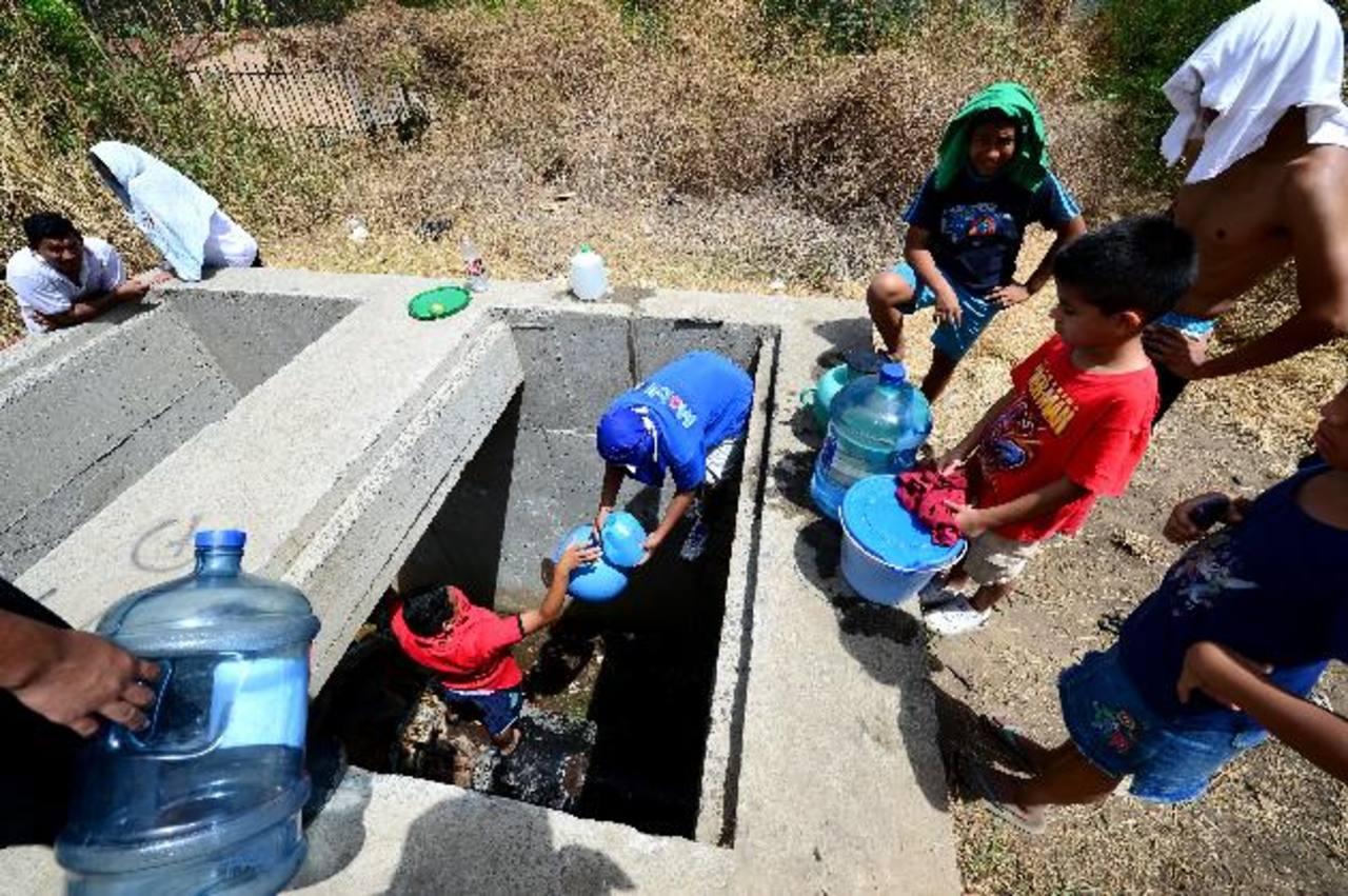 Niños y jóvenes han tenido que arriesgarse al obtener agua de un pozo. Fotos EDH/ mARIO aMAYA