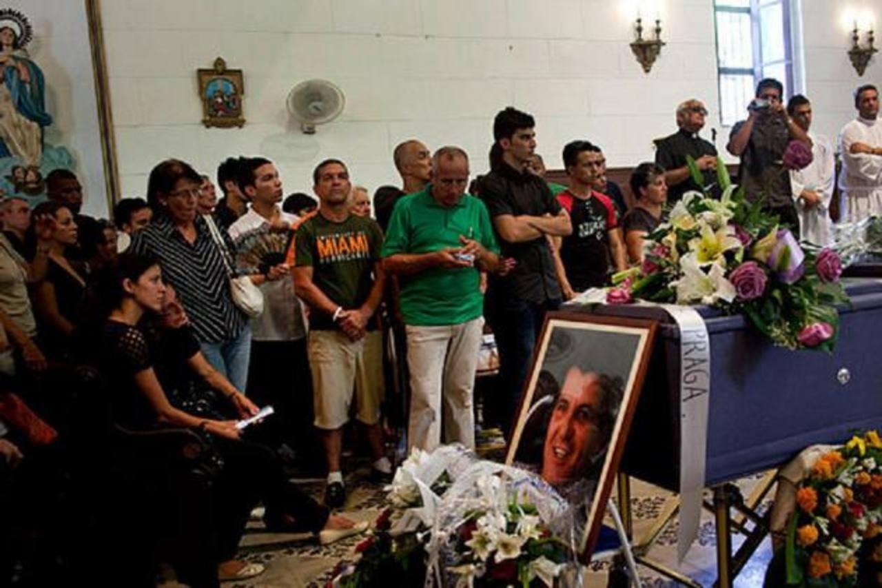 Cubanos velan el féretro con los restos del opositor Oswaldo Payá, el lunes 23 de julio de 2012. foto edh / internet