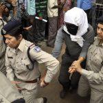 La mujer fue escoltada con una capucha que le tapaba la cara, ya que en India está prohibido exponer a las víctimas de violación . FOTO AP