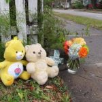 Dos osos de felpa, una cruz y un ramo de flores se colocaron cerca del lugar donde un bebé fue asesinado de un tiro en la caras. Foto/ AP