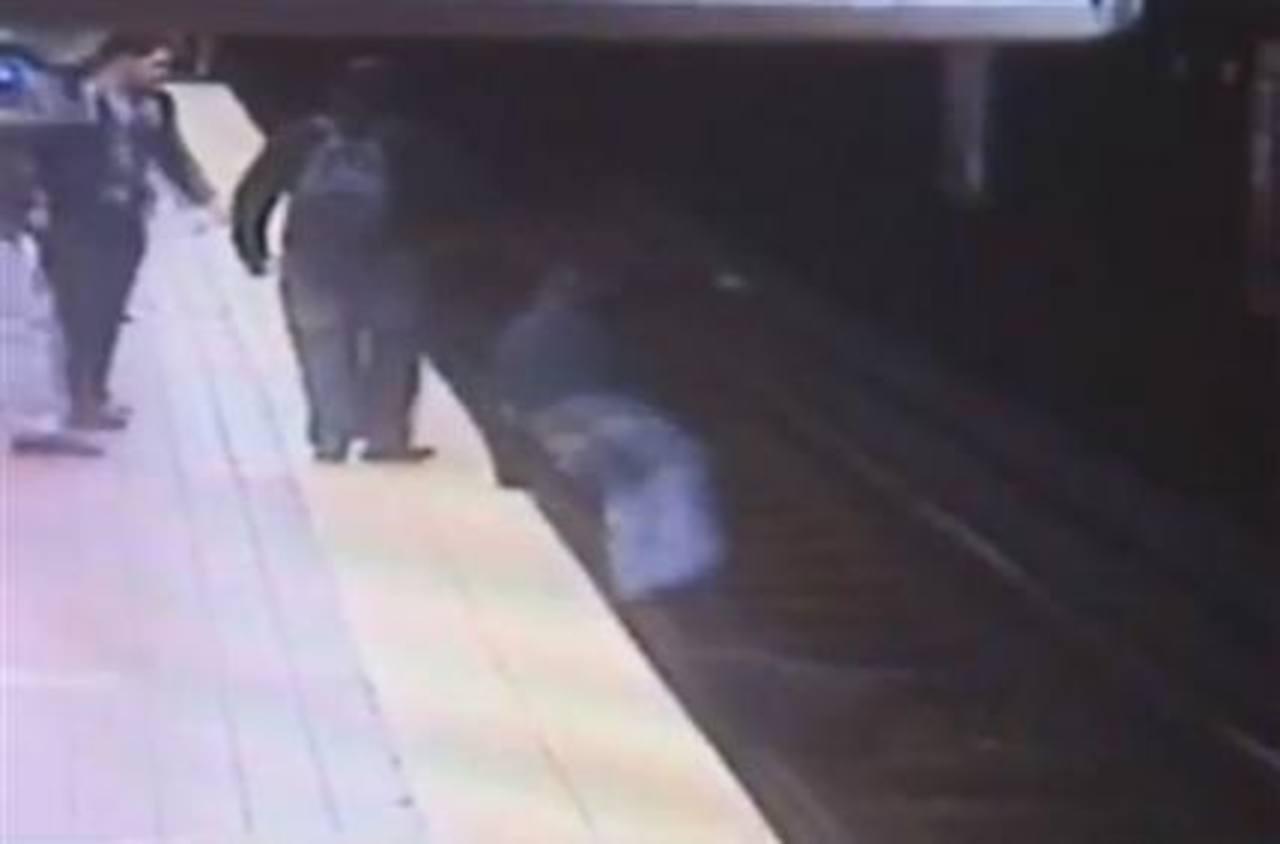 En esta imagen de un video de seguridad suministrada por la Autoridad de Transporte del Sudeste de Pensilvania, Christopher Knafelc salta a las vías del subterráneo en el norte de Filadelfia para ayudar a un hombre que se cayó de la plataforma el jue