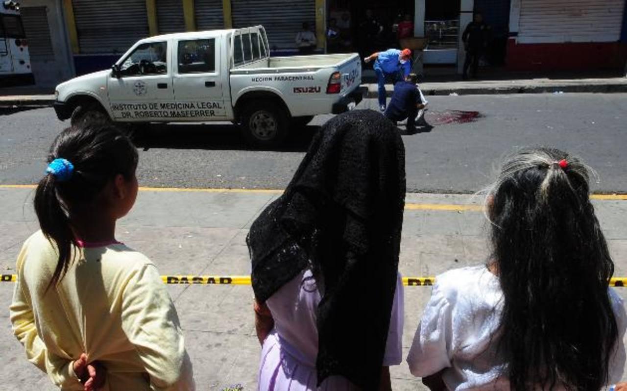 Señoras observan cuando Medicina Legal realiza el levantamiento del cadáver de Santiago Girón, de 76 años. Foto EDH / Lissette Lemus