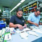 Empleados de droguerías colocan las nuevas etiquetas a los productos. Foto EDH / René Estrada