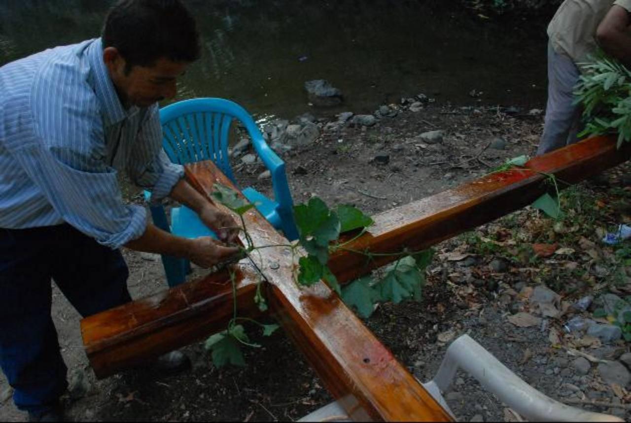 """Tras el """"baño"""" los hombres adornan la cruz con hojas y flores que encuentran a orillas del río. foto edh / archivo"""