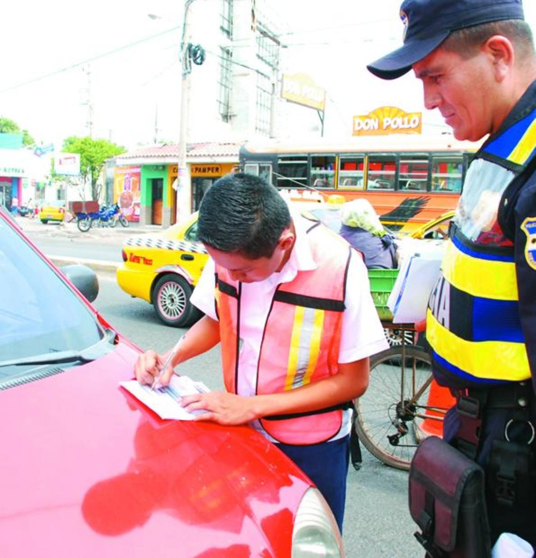 Estudiantes del sexto grado del Centro Escolar Sagrado Corazón colocan multas a conductores. Foto EDH /JENNY VENTURA