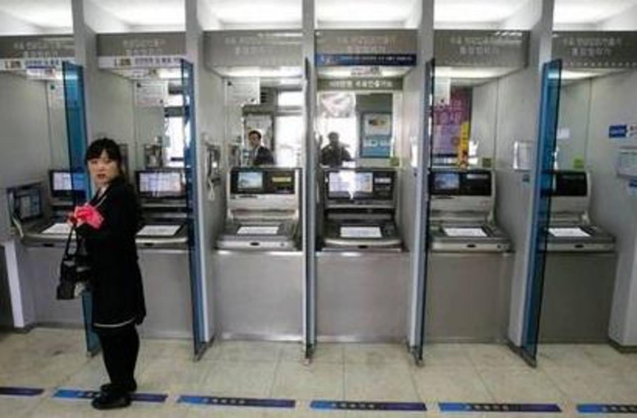 Una usuaria frente a una fila de cajeros automáticos en una sucursal del banco Shinhan después que se paralizaron las redes informáticas del banco en Seúl, Corea del Sur. Foto/ AP