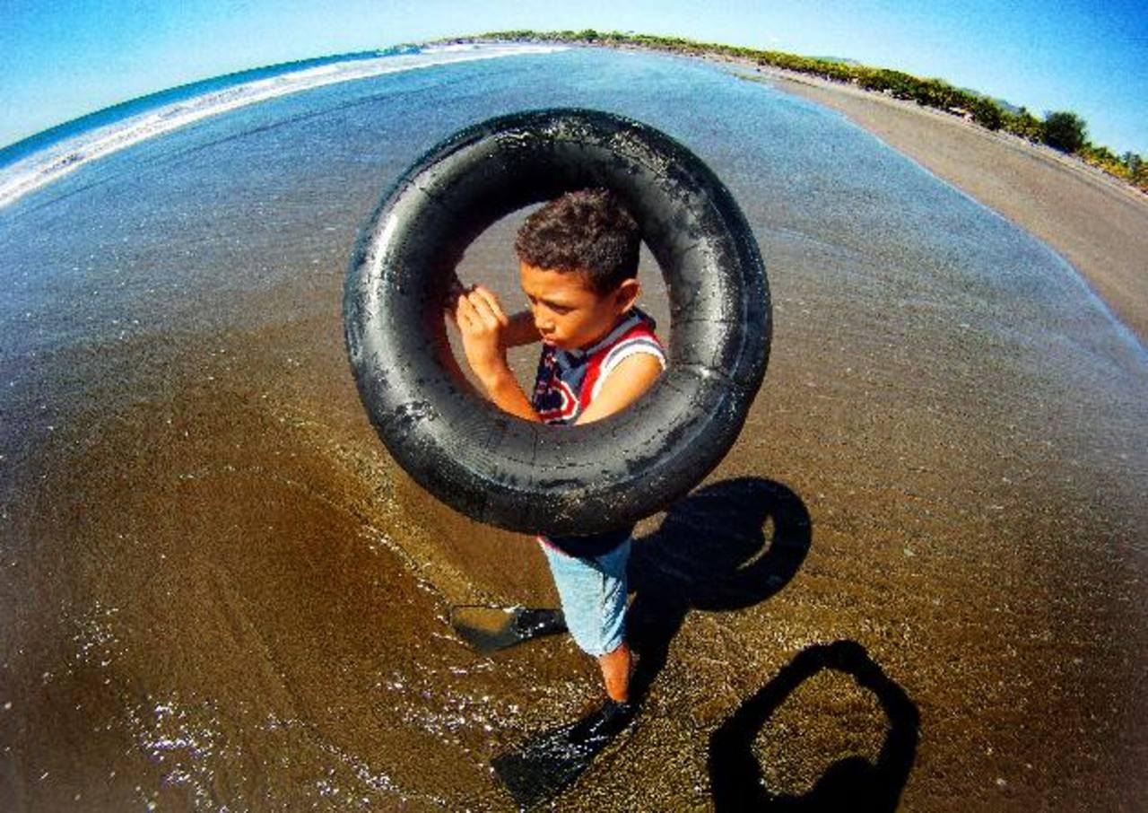 Ante la falta de una bomba, al pequeño no le queda otra que inflar el neumático que le sirve como flotador con la boca.