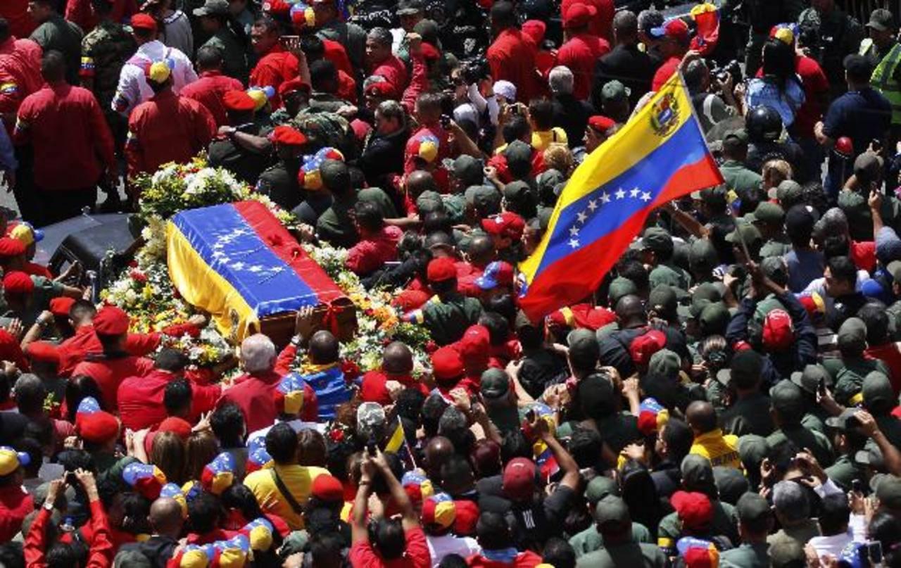 Marcha fúnebre. Simpatizantes de Chávez rodean el féretro con los restos del venezolano, durante el recorrido desde el Hospital Militar hasta la Academia Militar. foto edh/ AP