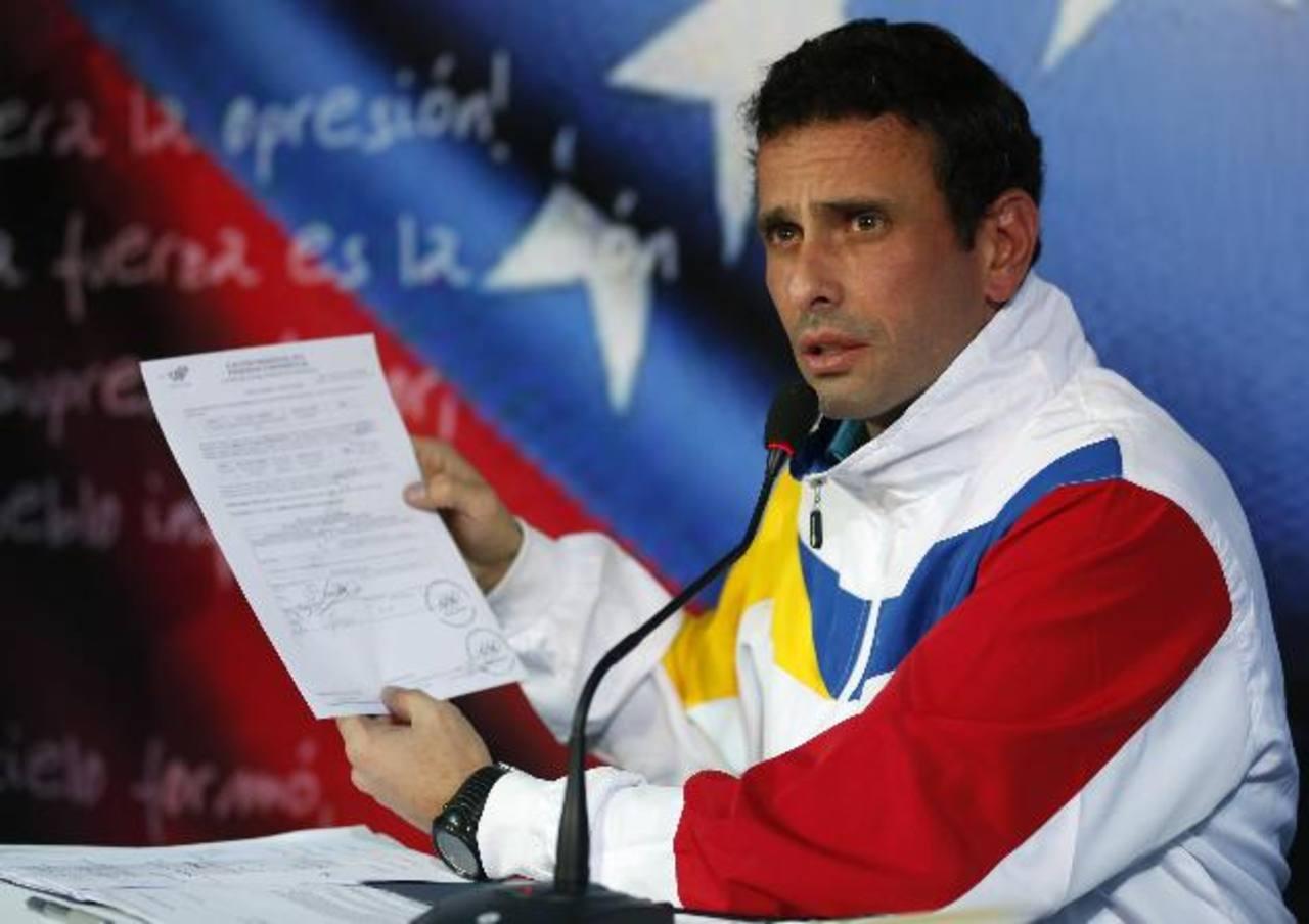 El candidato opositor Herique Capriles muestra su inscripción a las presidenciales.