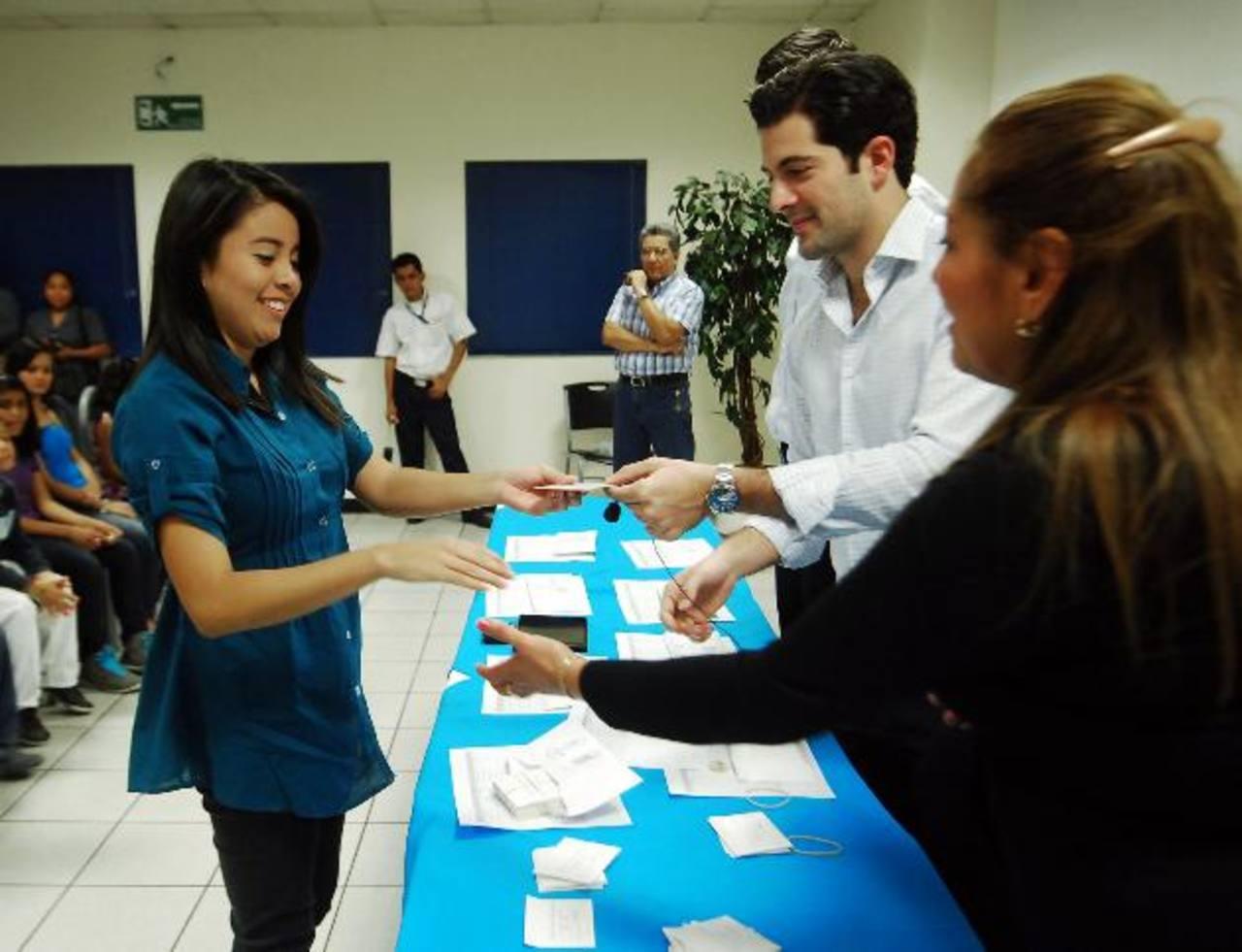 Los ejecutivos entregan incentivo a una de las beneficiadas. Foto EDH / Marlon Hernández
