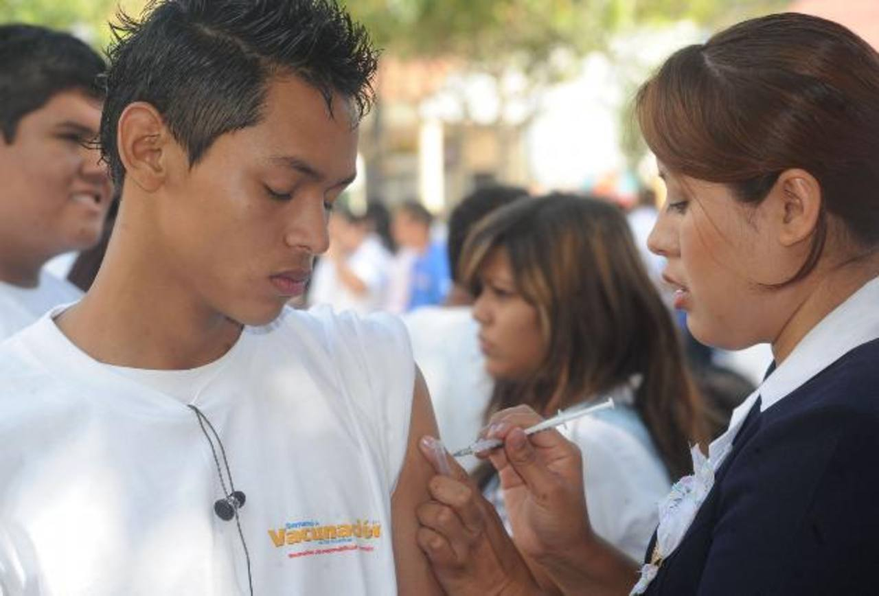 Un joven es vacunado en el Parque Daniel Hernández, en Santa Tecla.