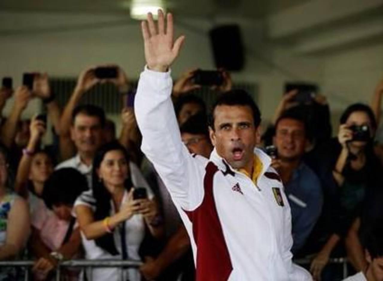 El candidato presidencial opositor Henrique Capriles saluda a su llegada a una casilla electoral para depositar su voto en las elecciones presidenciales, en Caracas, Venezuela