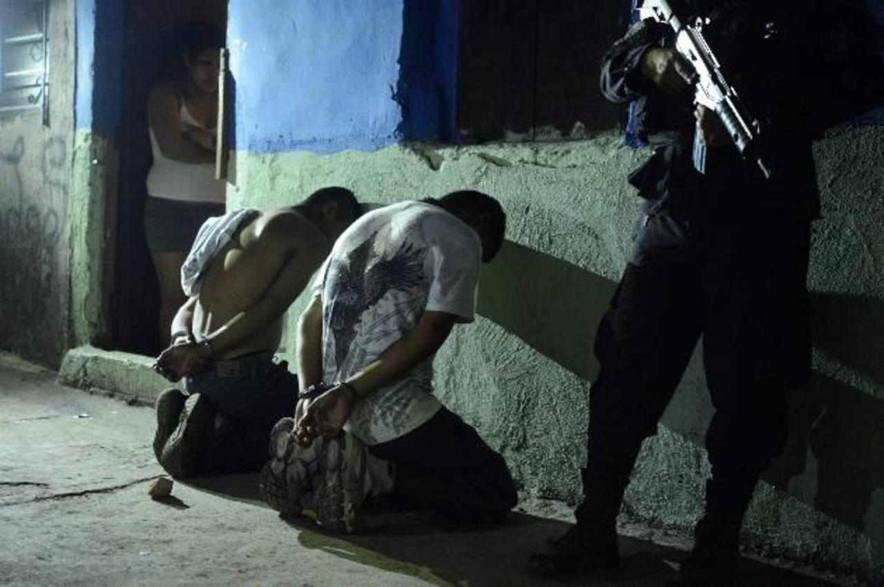 Un policía custodia a dos detenidos en el operativo realizado en distintas comunidades de Santa Tecla. Foto EDH / Marvin Recinos