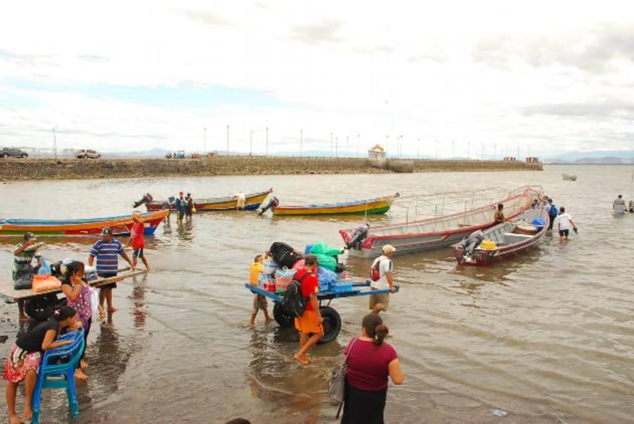 Personas de islas, deben cruzar por una cloaca para poder salir del agua a falta de un muelle adecuado. Foto EDH / insy mendoza