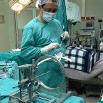 Uno de los especialistas prepara el equipo para realizar la cirugía a un hombre con parkinson.