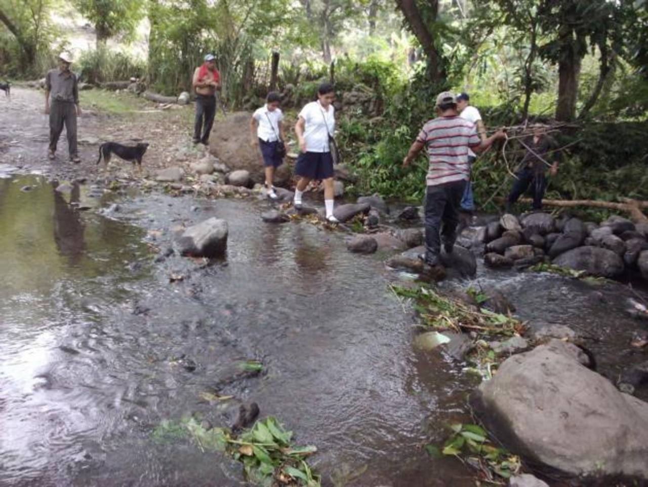 Pobladores tienen que esperar a que el cauce del río baje para cruzar al otro lado de la calle. Foto EDH / CORTESÍA