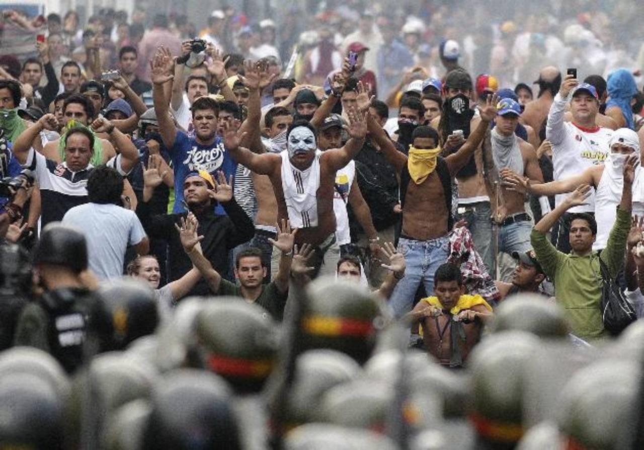 Opositores al gobierno chavista protestan en Caracas frente a las fuerzas militares oficiales, descontentos por los resultados electorales del domingo pasado que dejaron como perdedor al candidato Henrique Capriles. Foto EDH / reuters