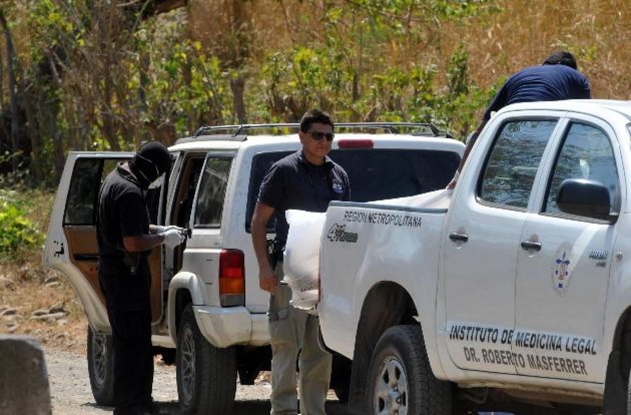 Policías registran el auto en el que las mujeres fueron mantenidas cautivas varias horas y luego acribilladas. Vivían en Estados Unidos. Foto EDH / Éricka Chávez