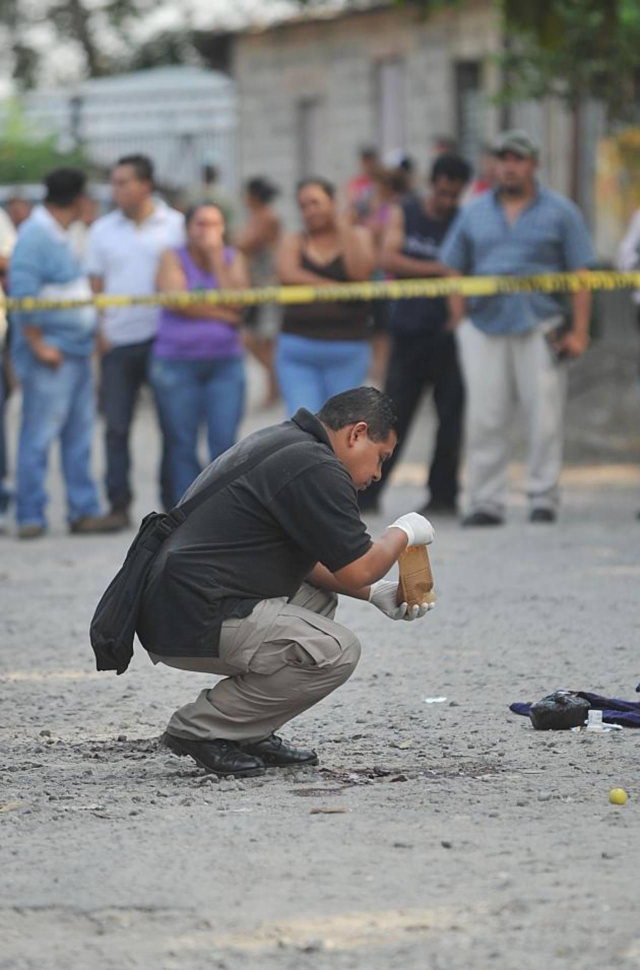 Investigador de la Policía levanta evidencias en el sitio donde ayer asesinaron a José Ismael Cornejo, en la calle principal de la colonia Las Flores, en Soyapango. Foto EDH / Óscar mira