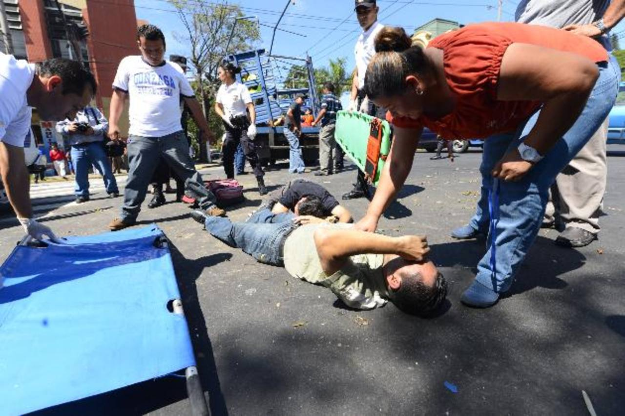 Personas particulares auxilian a dos de los tres policías golpeados. Foto EDH / Marvin Recinos