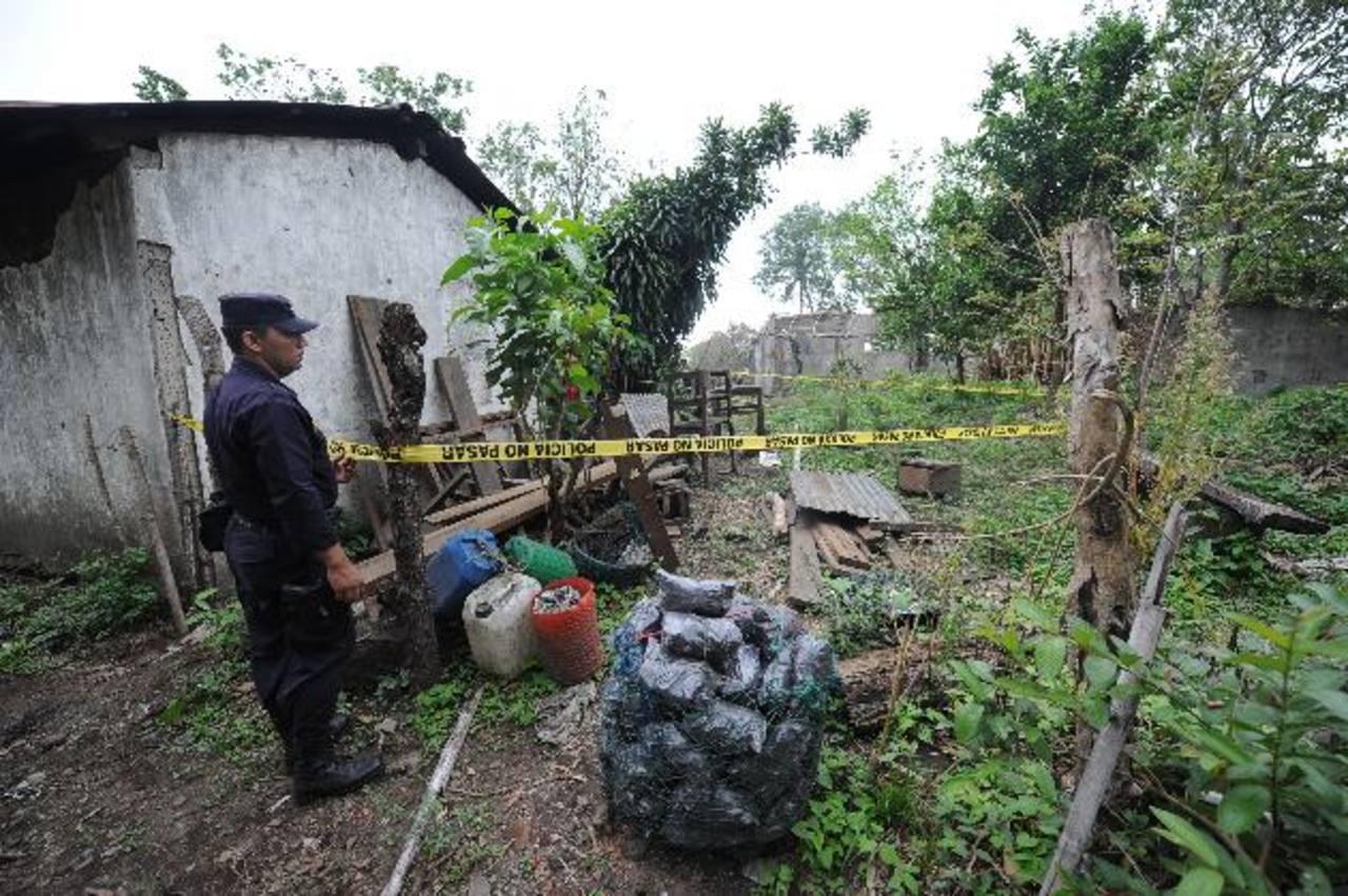 Un policía custodia la casa donde habitaban dos de las víctimas, en el cantón El Copinol, Zacatecoluca. Foto EDH / Douglas Urquilla