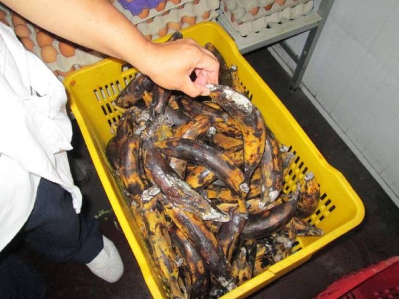 Un empleado del hospital Zacamil revisa parte de los alimentos arruinados.