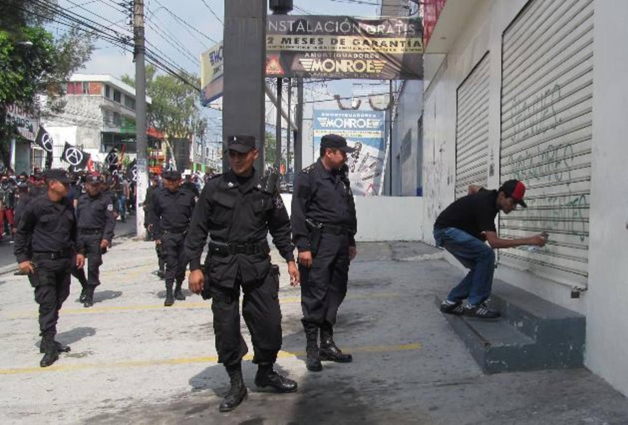Un inspector y un subinspector policial observan a un manifestante que mancha la cortina de un negocio que funciona en la 29 Calle Poniente de San Salvador. Foto EDH / Jorge Beltrán