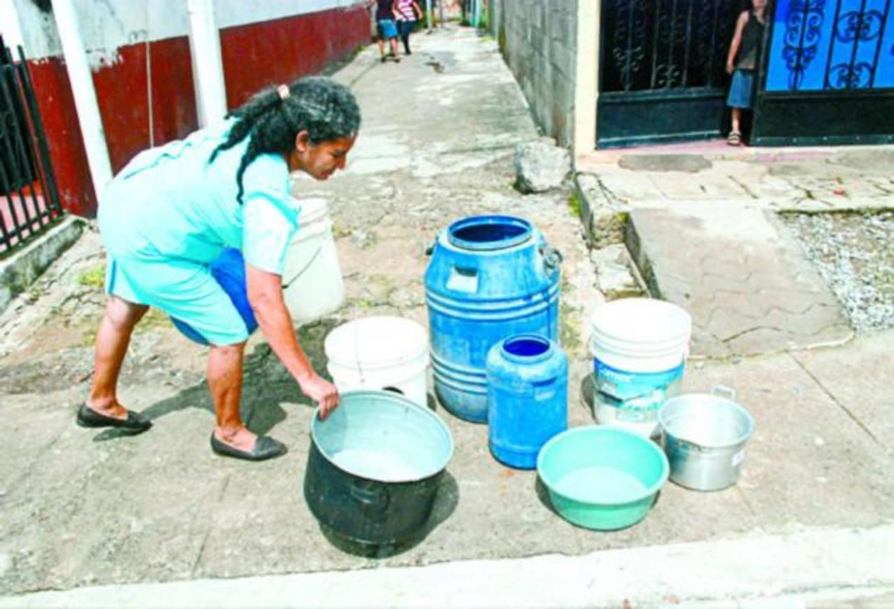 Los residentes de varias colonias sacan sus recipientes a las calles a la espera de que les lleven agua. Foto EDH / CRISTIAN DÍAZ