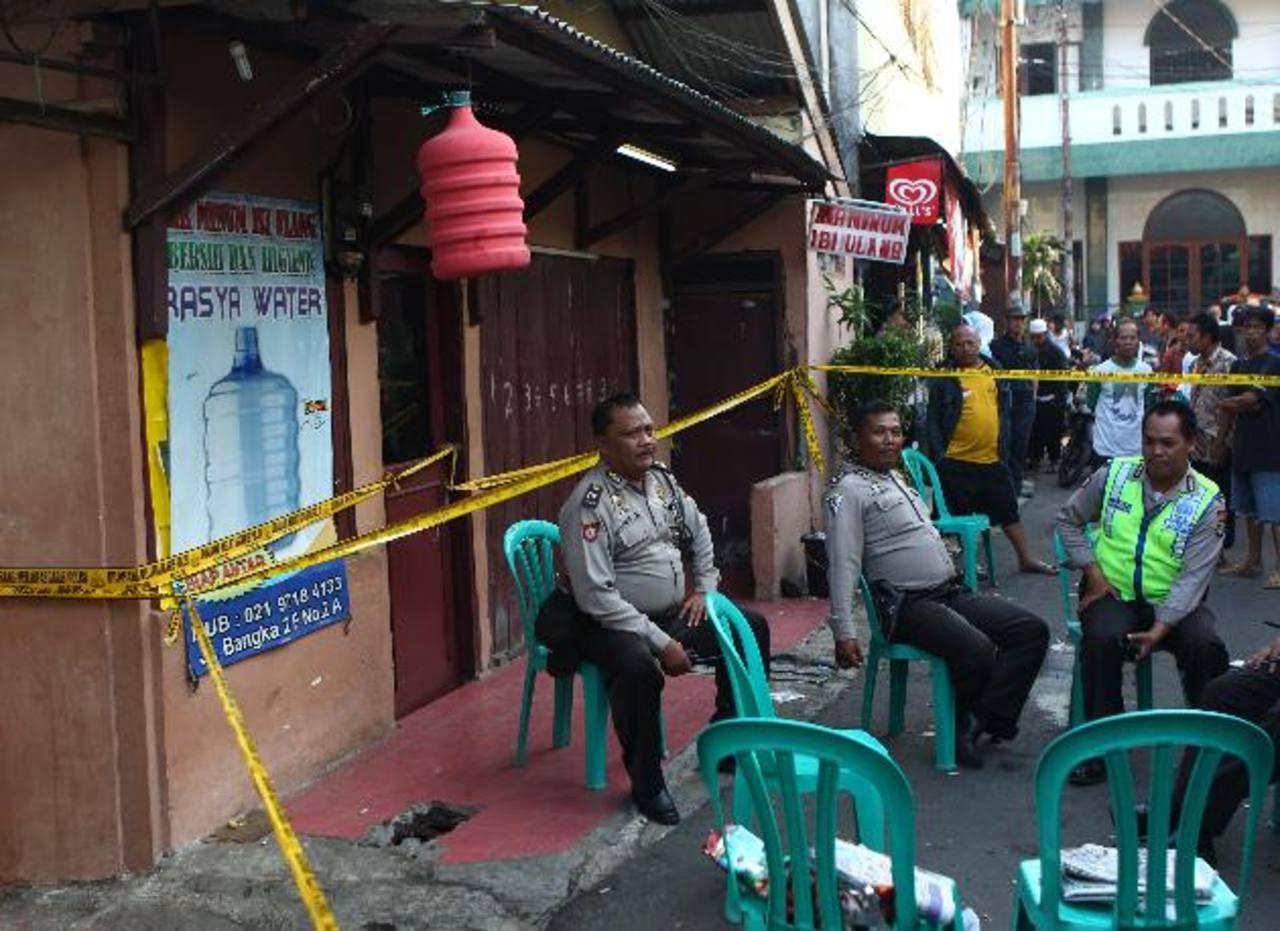 Varios agentes frente a la casa de Sefa Riano, presunto islamista detenido tras publicar sus planes de detonar explosivos en la embajada de Mianmar en su página de Facebook. Foto/ AP